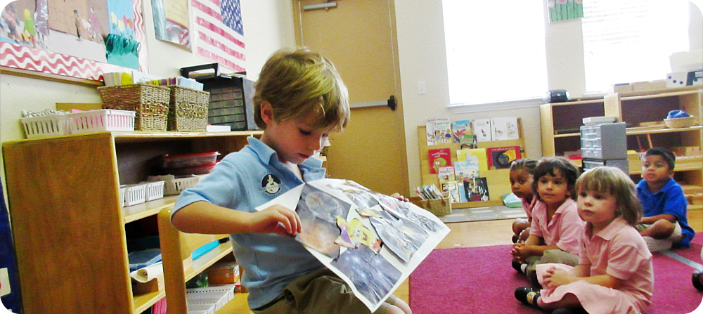 little boy showing his work to the class